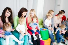 Group of mothers with kids. Group of mothers with their kids gathered to talk, toddlers have a launch Stock Images