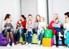 Group of mothers with kids. Young pretty mothers talking and babies are playing royalty free stock photos