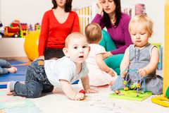 Group of mothers with their babies. Four moms with their lovely children in kindergarten Royalty Free Stock Photography