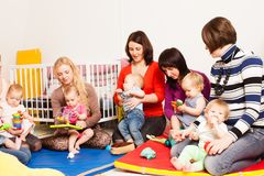 Group of mothers with their babies. Four moms with their lovely children in kindergarten Stock Photography
