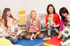 Group of mothers with their babies. Four moms with their lovely children in kindergarten Royalty Free Stock Photo