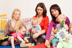 Group of mothers with their babies. Four moms with their lovely children in kindergarten Royalty Free Stock Images