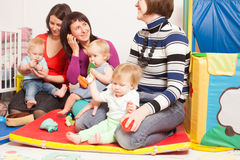 Group of mothers with their babies. Four moms with their lovely children in kindergarten Stock Photo