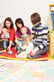 Group of mothers with their babies. Moms with their lovely children in kindergarten Stock Photography