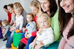 Group of mothers with kids. Group of mothers with their kids gathered to talk, toddlers have a launch Royalty Free Stock Photos