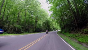 Group of Motorcyclists Pass Car on Mountain Road. A car driving the highway through the Great Smoky Mountain National Park passes a group of motorcyclists stock footage