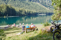 Group of mountain bikers taking a rest at beautiful lake Vordere Royalty Free Stock Photography
