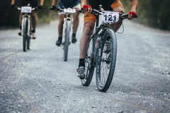 Group mountain bikers turns gravel road Stock Photos