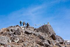 Group of Mountain Climbers approaching to rocky Summit with buddhist Flags Stock Photography