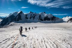 Group of Mountaineers with Backpacks is Roped Together and Ascen royalty free stock photo