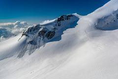 A group of mountaineers climb up a glacier towards the pak of the Allalinhorn stock photos