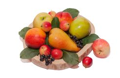 Group of multi-colored fruit on a wooden handmade plate . stock photography