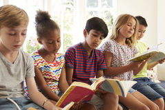 Group Of Multi-Cultural Children Reading On Window Seat royalty free stock photography