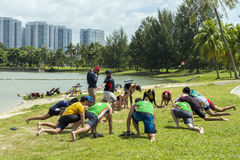 Group of multi-cultural men and women do warm up before sport event at Kallang river. Stock Image
