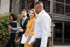 Group of multi-ethnic business people waking outside office buil stock images