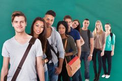 Student Standing In Row Against Green Background. Group Of Multi-ethnic College Student Standing In Row Against Green Background Royalty Free Stock Photos
