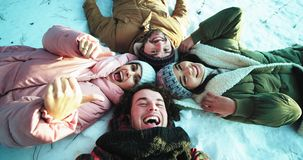 Group of multi ethnic friends enjoying the time together in a winter time they laying down on the floor make a circle. And make a funny faces and enjoying the stock footage