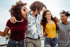 Group of multi-ethnic friends having fun outdoors. Four young people walking outdoors together. Group of multi-ethnic men and women having fun outdoors royalty free stock photo