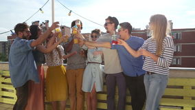 Group of multi-ethnic friends standing at rooftop and toasting. Group of cheerful multi-ethnic friends standing on the rooftop terrace and toasting stock footage