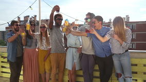 Group of multi-ethnic friends standing at rooftop and toasting. Group of cheerful multi-ethnic friends standing on the rooftop terrace and toasting stock video footage