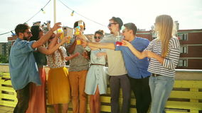 Group of multi-ethnic friends standing at rooftop and toasting. Group of cheerful multi-ethnic friends standing on the rooftop terrace and toasting, graded stock footage