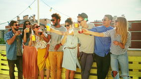 Group of multi-ethnic friends standing at rooftop and toasting. Group of cheerful multi-ethnic friends standing on the rooftop terrace and toasting, graded stock video