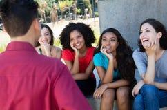 Group of multi ethnic girls flirting with one guy Royalty Free Stock Image