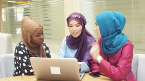 Group of multi-ethnic Muslim business ladies sit in cafe and making online purchases using a laptop. Group of multi-ethnic Muslim business ladies sit in cafe stock video footage