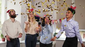 Group of multi-ethnic office workers partying in the office throwing golden confetti, blowing confetti from hands. Wearing christmas hats and celebrating stock video