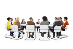 Group of Multi-Ethnic People in a Meeting. And Social Networking Related Symbols Above Royalty Free Stock Photography