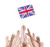 Group of multi-ethnic people reaching for and holding the flag o Royalty Free Stock Photos