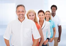 Group of multi-ethnic people standing in a row. Group Of Happy Multi-racial People Standing In A Row Stock Photos