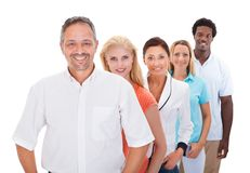 Group of multi-ethnic people standing in a row. Group Of Multi-racial People Standing In A Row On White Background Royalty Free Stock Photos