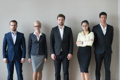 Young and mature business people standing together in row Stock Images