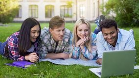 Group of multi-ethnic students relaxing on grass and watching video on laptop stock images