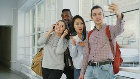 Group of multi-ethnic students taking selfie on smartphone camera while standing in corridor of university . Hipster guy. Group of four multi-ethnic students stock video
