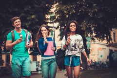 Group of multi ethnic students walking in a city.  Stock Photo