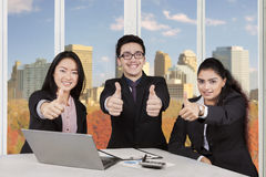 Group of multi ethnic workers show thumbs up Stock Photos