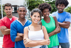 Group of multi ethnic young adults with crossed arms in city. Group of multi ethnic young adults with crossed arms in the city with buildings and green plants Royalty Free Stock Images