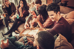 Group of multi ethnic young friends eating pizza in home interior Royalty Free Stock Image