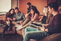Group of multi ethnic young students preparing for exams in home interior Royalty Free Stock Images