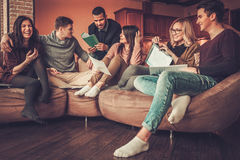 Group of multi ethnic young students preparing for exams in home interior Stock Images