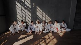 A group of multi ethnic young teenagers are sitting against a wall in the sunshine in a martial arts taekwondo class stock video footage