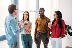 Group of multicultural business people having conversation during coffee break. In office royalty free stock images