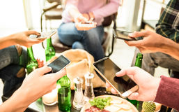 Group of multicultural friends having fun on mobile cell phones. Group of multicultural friends having fun on smartphone at bar - People hands using mobile smart Stock Photo