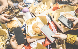 Group of multicultural friends having fun on smartphone at restaurant - Multiracial people hands using mobile smart phone at food stock images
