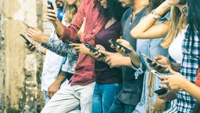 Group of multicultural friends using mobile smart phone. Group of multicultural friends using smartphone outdoors - People hands addicted by mobile smart phone Stock Photo