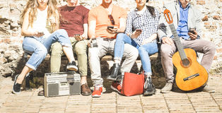 Group of multicultural friends using smartphone on urban background stock photo