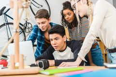 group of multicultural teens using laptop stock image