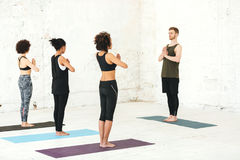 Group of multicultural women practicing yoga with male instructor royalty free stock photography